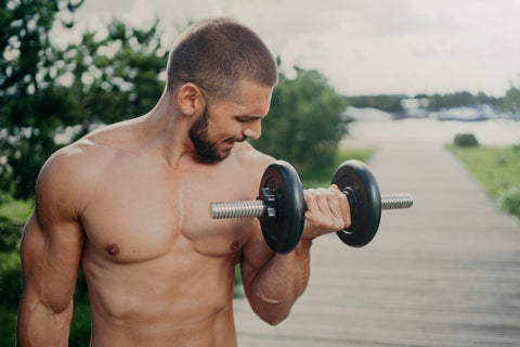 Man curing dumbness while looking at bicep