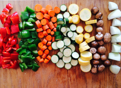 Lines of cut up peppers, cucumber, onion, and other vegetables