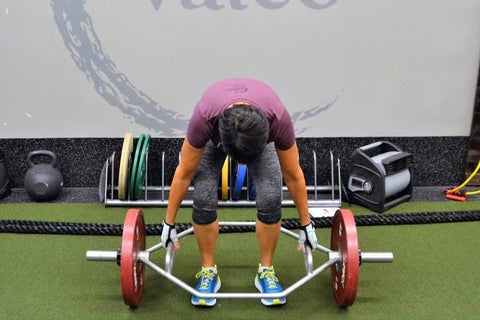 Woman inside of round bar about to do a deadlift with face looking down