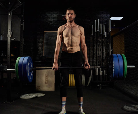 Man standing up deadlifting bar with 4 plates on each side in dark gym