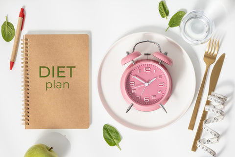 """Notebook with """"Diet Plan"""" and plate with alarm clock"""
