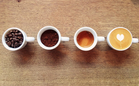 Four lined up cups of coffee with different types of caffeine in each