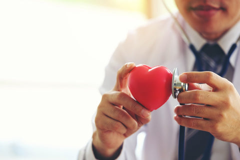 Doctor holding a stethoscope up to plastic heart