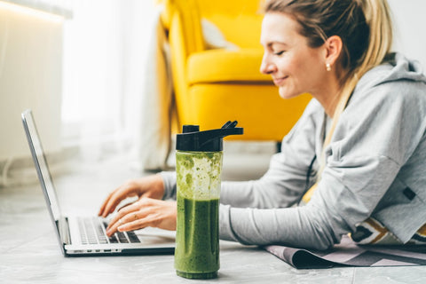 Woman typing on laptop with shake next to her