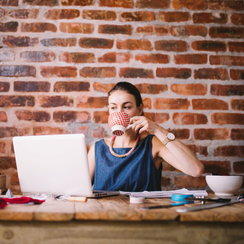 Woman at desk in front of computer drinking coffee while working