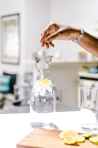 Hand dropping lemons into jar of water