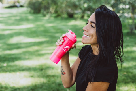 Woman drinking EAA from a shaker bottle in a park.