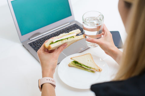 Woman holding sandwich and glass of water while looking at laptop