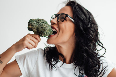Side view of woman taking bite from broccoli
