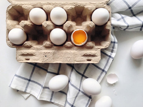 Egg carton with missing eggs and cracked egg