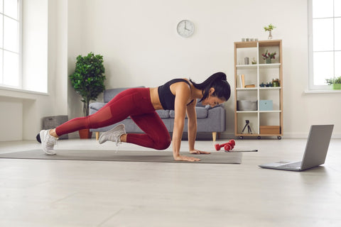 Woman on yoga mat in house doing exercise program off laptop
