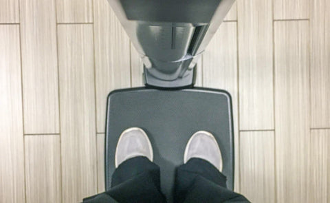 Looking down at feet standing on a weight scale