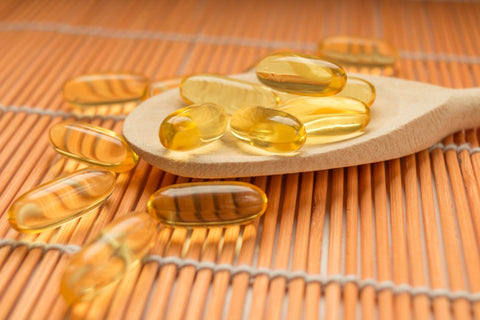 Fish oil capsules on spoon and falling off
