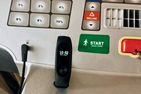 Fitness tracker clip on with treadmill screen in background
