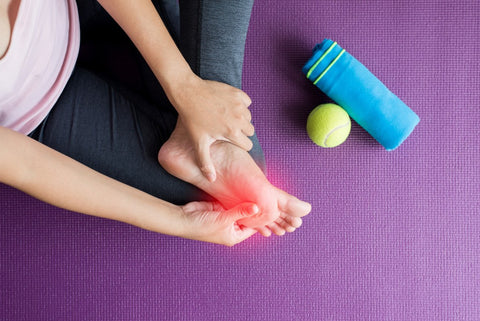 Woman holding cramping foot on yoga mat next to tennis ball and towel