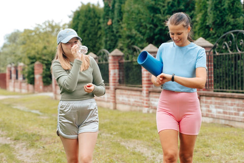 Two girls smiling after workout and looking at watch