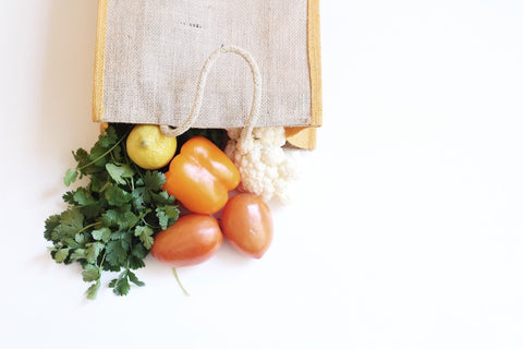 Cloth bag with fruits and vegetables coming out