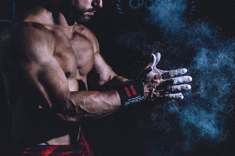 Shirtless man clapping with powder on his hands in the gym