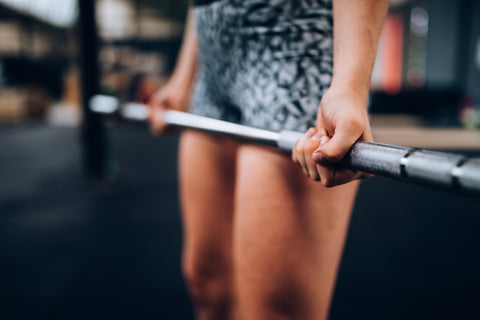 Close up of woman's hands on barbell
