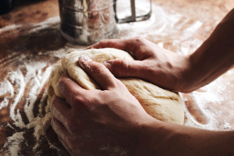 Two hands needing dough with flour around it