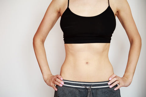 woman in sports bra and sweats with hands on hips