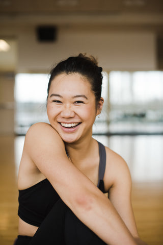 Smiling lady stretching arm across body