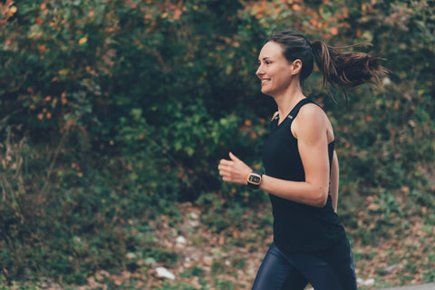 Side view of happy woman running in woods