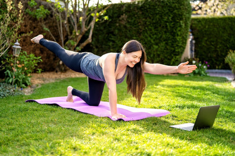 Woman doing yoga pose on purple mat while looking at laptop