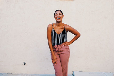 Happy young lady standing with hand on hip laughing and smiling