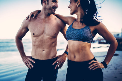 Woman with arm around man looking at each other after workout