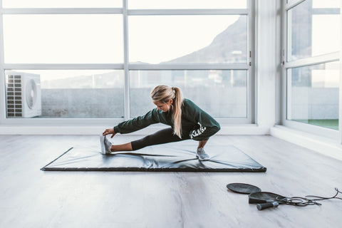 Woman stretching touching toes on workout mat in room of glass windows