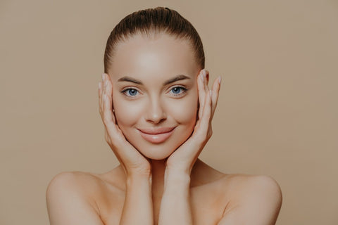 Woman smiling with clear skin hands around face
