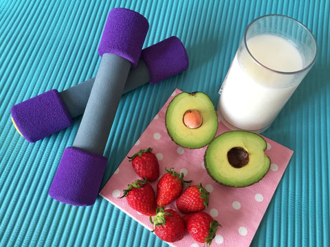 Weights next to avocado, strawberry and milk snack
