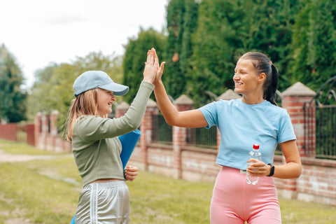 Two women high fiving after a workout