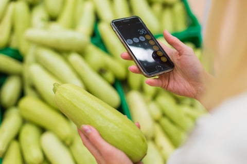 Person holding squash while on phone calculator