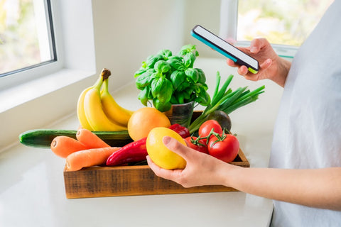 Woman holding orange in front of basket of fruit while logging it on phone
