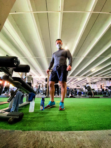 Man standing in gym with mask on near bench