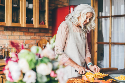 Woman cooking and focusing on intuitive eating.