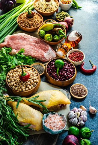 Keto ingredients laid out on a table such as meat, grains, beans, and vegetables