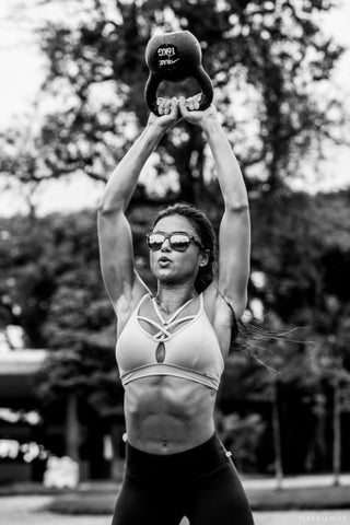Crossfit woman holding kettlebell above head with straight arms