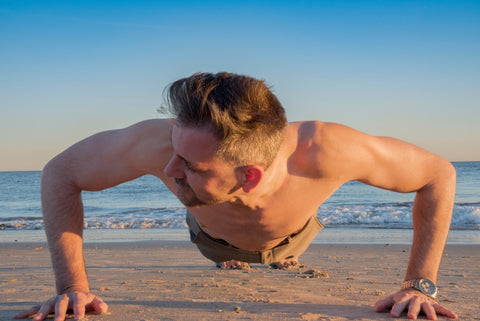 Man looking to side while doing pushup on sand