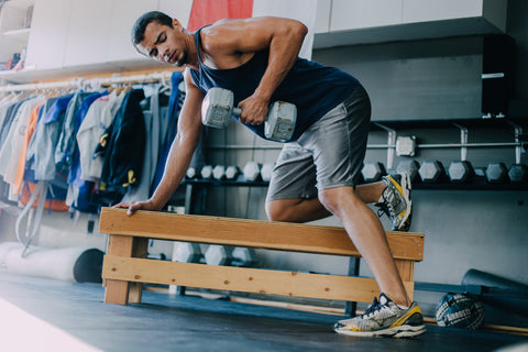 Man lifting dumbbell while leaning on wooden bench