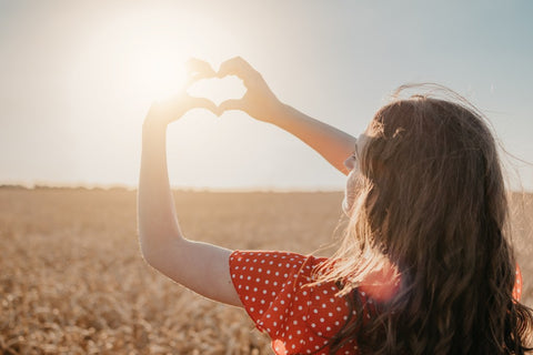 Girl making a heart around the sun in the sky