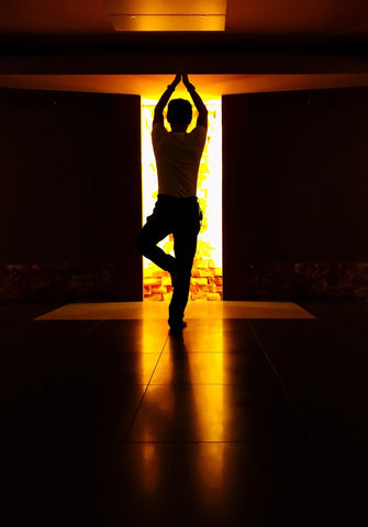 Man doing hot yoga in front of door with light shining through creating halo effect
