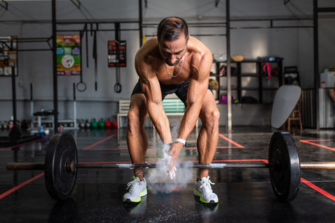 Man bending over weight bar while clapping hands and releasing powder