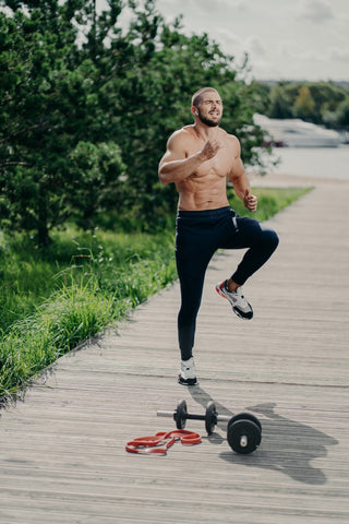 Man doing high knees on boardwalk with weights next to him