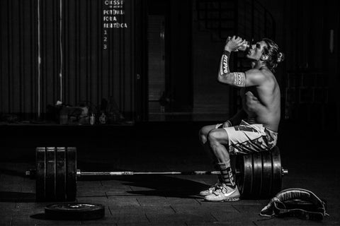 Man drinking supplement while sitting on barbell