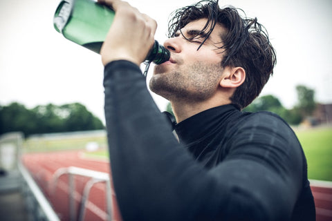 Close up of man on a track drinking from a water bottle