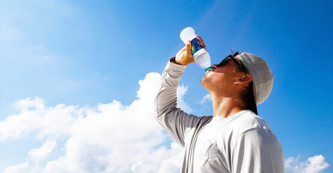 Man drinking water in front of blue sky