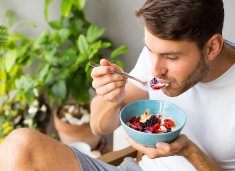 Man eating fruit bowl with spoon